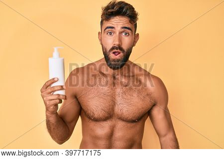 Young hispanic man standing shirtless holding sunscreen lotion scared and amazed with open mouth for surprise, disbelief face