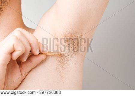 Man Remove Hair Using Tweezers From Armpit. Unshaved Armpits Or Underarm. Depilation And Hair Remove
