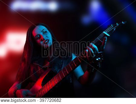 Young Attractive Redheaded Rocker Woman Playing The Electric Guitar