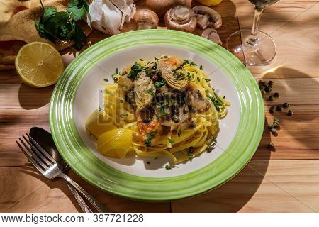 Italian Chicken Piccata Linguine With Mushrooms Artichoke Hearts And Capers Paired With Glass Of Dry