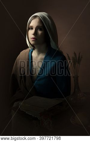 Portrait Of A Young Girl Who Looks Into The Camera. Renaissance. A Woman In A Retro Dress. Historica