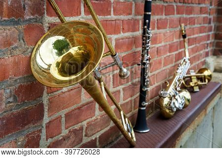 Musical Instruments Including Trombone Trumpet Clarinet And Saxophone On Brick Wall Outside Jazz Clu