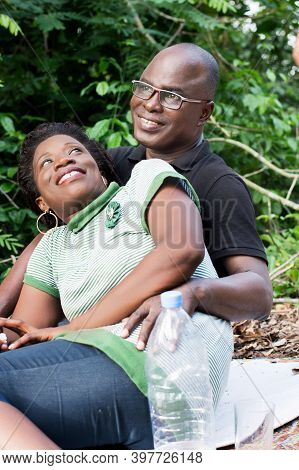 Portrait Of Happy Loving Couple Sitting In The Forest. Sitting On A White Sheet Young Woman Smiling