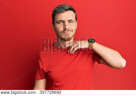 Handsome caucasian man wearing casual red tshirt cutting throat with hand as knife, threaten aggression with furious violence