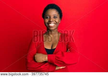Young african woman with afro hair wearing casual clothes over red background happy face smiling with crossed arms looking at the camera. positive person.