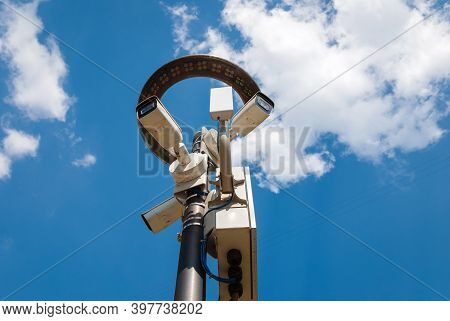 Outdoor Surveillance Cameras On Lamppost With Led Lantern Against Blue Sky