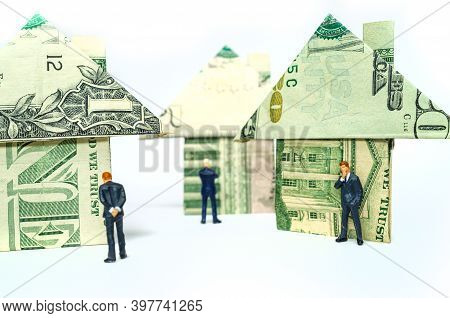 Miniature Figurine Businessmen And Origami Paper Money Houses For Real Estate And Housing Market Con