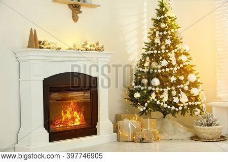 Decorated Christmas Tree With Faux Fur Skirt And Gift Boxes Near Fireplace Indoors