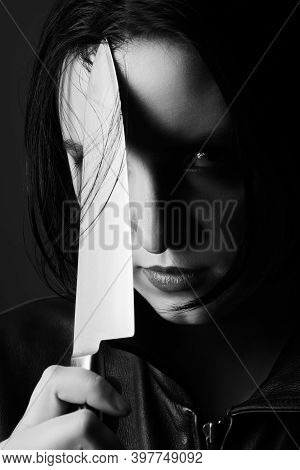 Serious Young Woman With Knife Looking At Camera Closeup Portrait, Monochrome