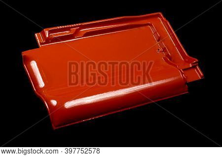 Single New Shinny Red Roof Tile Isolated On The Black Background