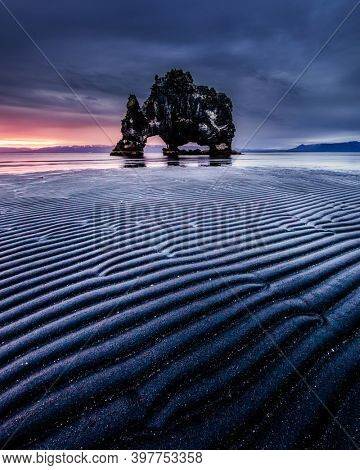 Unique and strange rock on the shore of the ocean at low tide. Location place Hvitserkur, Vatnsnes peninsula, Iceland, Europe. Scenic image of exotic world landmarks. Discover the beauty of earth.