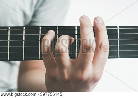 Male Hand Holding A Barre Chord On The Acoustic Guitar, Close-up.