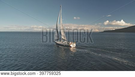 Luxury yacht sailing at ocean bay aerial. Passenger sailboat race at open sea near Arran Island, Scotland, Europe. Epic summer cruise on boat at cinematic soft light drone shot