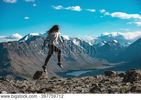 Beautiful Slim Sporty Girl Jumps Over Small Stone In High Mountains