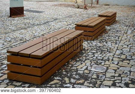 Paving Gray Brown Beige Color Of Natural Stone Boulders Of Irregular Shapes And Colors. Benches Arou