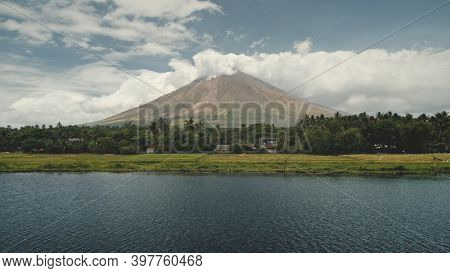Volcano erupt at green lake shore aerial. Philippines coutryside of Legazpi town at greenery meadows, palm trees. Small cottages at tropic forest. Tropical nobody nature landscape drone shot