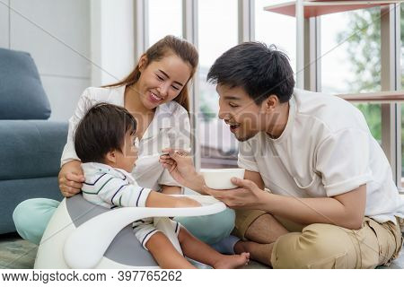 Asian Father Feeding His 6 Months Old Baby Boy With Solid Food With Spoon And Mother Sitting Near To