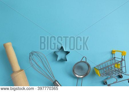 Different Baking Tools With Shopping Grocery Cart On Blue Background, Top View. Baking And Cooking I