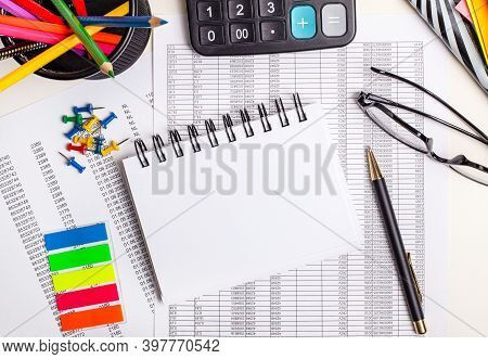 On The Reports There Is A White Blank Notebook With A Place To Insert Text, A Calculator, Glasses, B