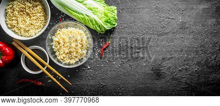 Instant Noodles In Bowls With Peking Cabbage And Soy Sauce. On Black Rustic Background