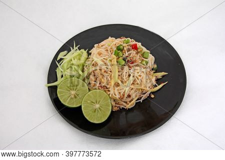 Thai Vermicelli Eaten Spicy Blend With Mackerel In The Black Dish, Food Decoration With Lemon, Chili