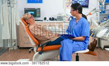 Nurse Explaining Medical Procedure To Senior Patient Waiting Dentist Doctor In Stomatological Room.