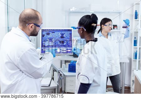 African Doctor And Scientist Working Conducting Virus Experiment Using Computer Software. Multiethni