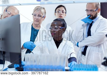 Multiethnic Group Of Laboratory Scientists Discussing Their Research In Front Of Computer. African H