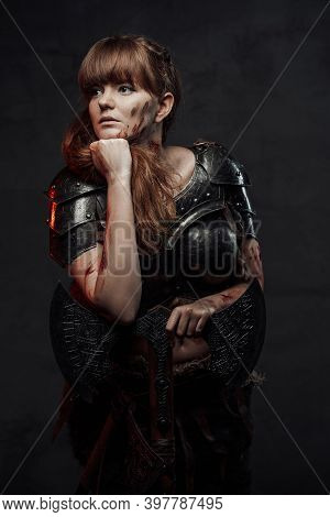 Portrait Of Posing In Dark Background Female Viking With Huge Axe And Grimy Face Dressed In Dark Arm
