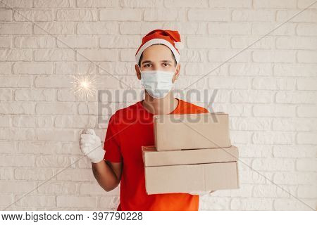 Young Delivery Service Man In Protective Face Mask, Medical Gloves Hold Cardboard Boxes, Sparkler In