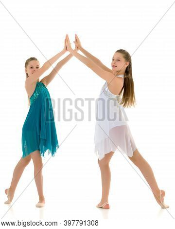 Pretty Gymnasts Performing Rhythmic Gymnastics Exercise Holding Each Other Hand And Raising It Over