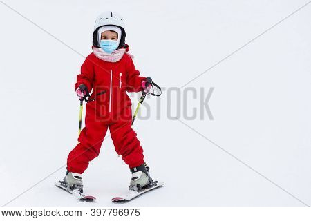 Portrait Of A Little Girl Skier In Medical Mask During Covid-19 Coronavirus On A Snowy Mountain At A