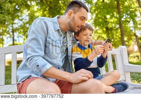 family, fatherhood and technology concept - happy father and little son with smartphone sitting on bench at summer park