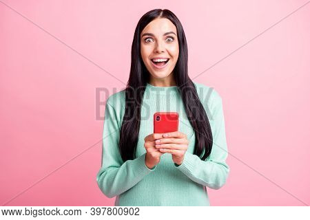 Photo Portrait Of Ecstatic Woman Holding Phone With Two Hands Isolated On Pastel Pink Colored Backgr