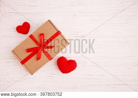 Valentine Handmade Present With Red Knitted Hearts And Gift Box. Present Box Of Gift On White Wooden