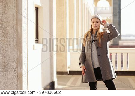 Blond Girl In Knitted Hat And Coat With Maple Leaf Close Up Portrait On City Architecture Background