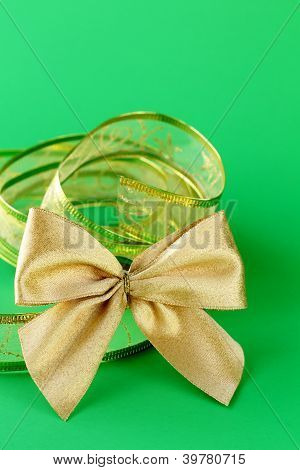 gold bow and ribbon  on a green background