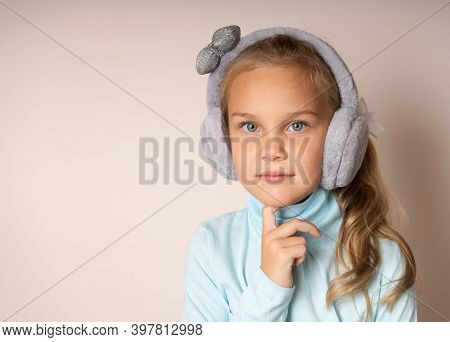 Cute Girl In Fur Headphones Looks At You Thoughtfully, Resting Her Chin On Her Hand