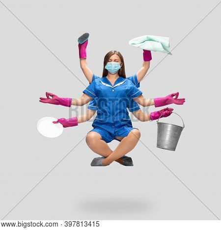Safety. Young Housemaid In Blue Uniform, Pink Gloves Nad Face Mask Like Shiva Isolated On Gray Backg
