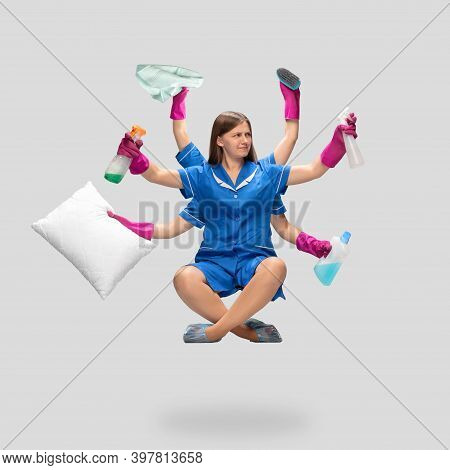 Portrait Of Female Housemaid In Blue Uniform Multitask Like Shiva Isolated On Gray Background. Young