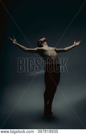 Inspiration. Young Graceful Male Ballet Dancer In Minimal Black Style Isolated On Dark Studio Backgr
