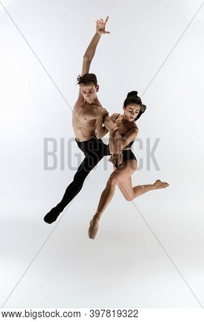 Ballet Jump. Young And Graceful Ballet Dancers In Black Style Isolated On White Studio Background. A