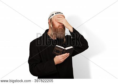 Religious Jewish Man Holding Siddur In His Hand Covering Eyes With Hand Isolated On White Background