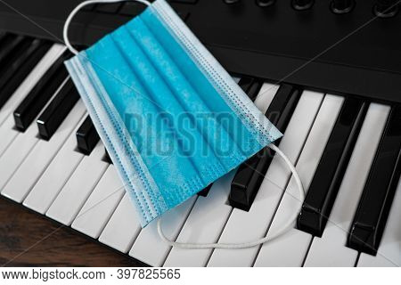 Piano And Medical Mask In Music Studio. Covid-19 Restrictions Concept.