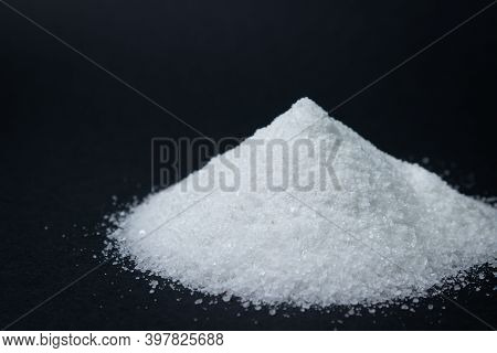 Heap Of Salt On A Black Background. Excessive Salt Intake. Coarse Salt