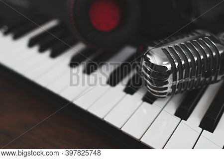 Headphones And Microphone On The Piano Keyboard. Recording Studio Concept.