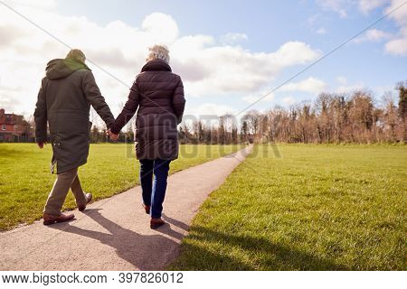 Rear View Of Loving Senior Couple Holding Hands Enjoying Autumn Or Winter Walk Through Park Together