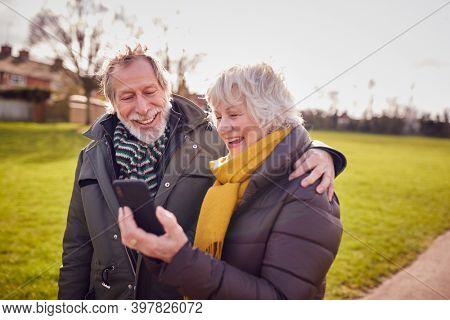 Loving Senior Couple Looking At Mobile Phone Enjoying Autumn Or Winter Walk Through Park Together