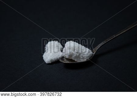 Salt On A Black Background. Spoon With Three Pieces Of Salt. Coarse Salt. Excessive Salt Intake.