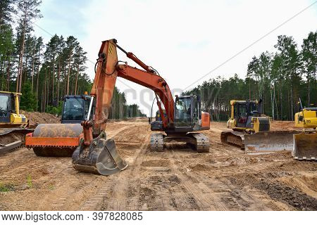Bulldozer, Excavator And Soil Compactor On Road Work. Earth-moving Heavy Equipment And Construction